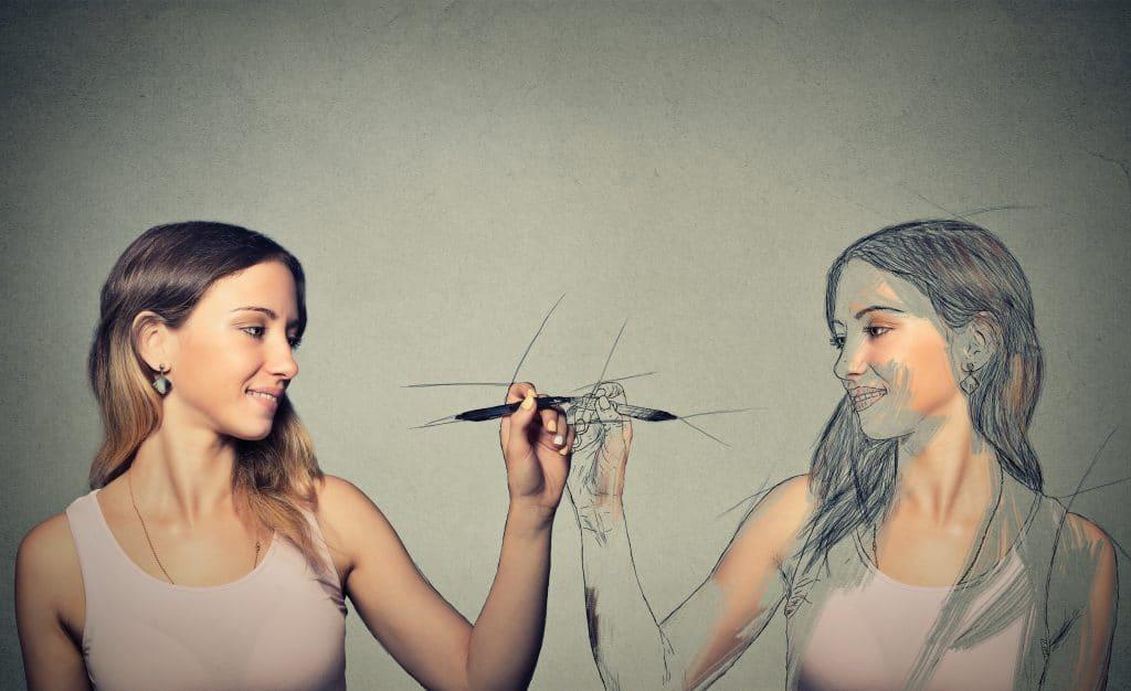 Imagem de uma mulher fazendo o desenho de sua auto imagem.