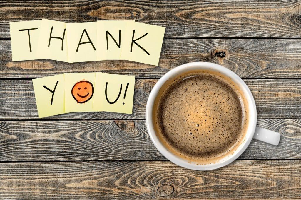 Bilhete escrito Thank You em smile. Ao lado do bilhete uma xícara branca cheia de café. Ambos estão colocados sobre uma mesa de madeira.