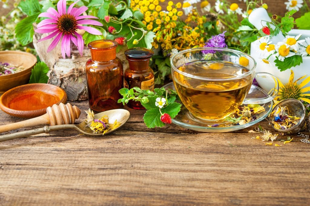 Chá de camomila dentro de uma xícata de vidro com pires. Ele está servido sobre uma mesa de madeira toda decorada com uma variedade de flores e mel.