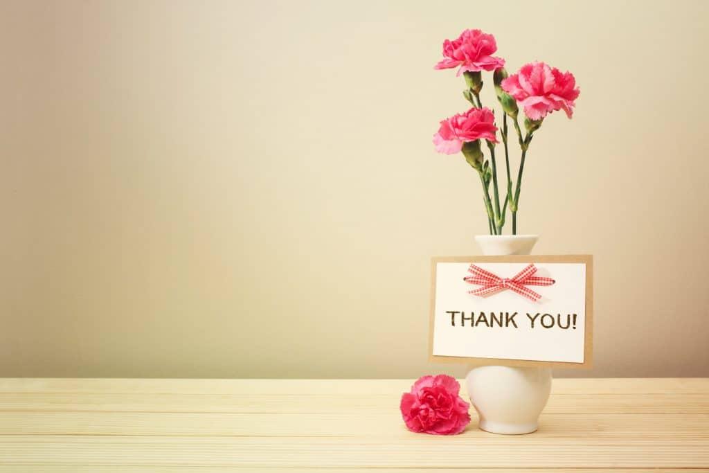 Vaso branco com três flores de cravos avermelhadas. Alguns botões da flor ainda estão fechados. No vaso está pendurado uma plaquinha escrita THANK YOU.