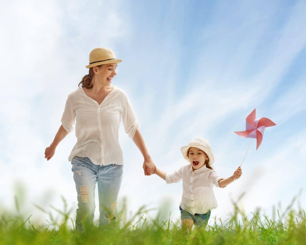 Mãe e criança feliz. Elas estão de mãos dadas caminhando em um campo bem verdinho. Elas estão vestidas iguais (chapéu de palha, camisa branca e jeans). A garotinha segura um catavento em uma das suas mãos.