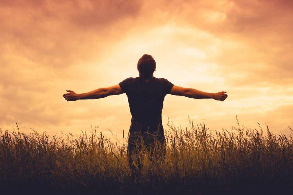 Homem de costas e de braços abertos fazendo uma oração de gratidão olhando para o sol se pondo.
