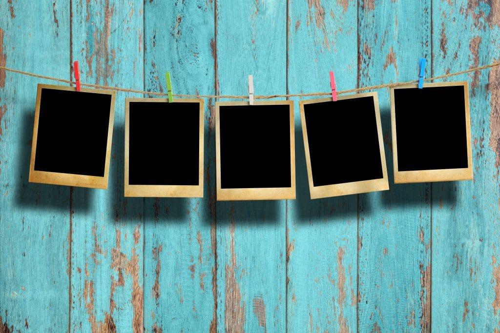 Painel com fundo de mandeira azul feito de barbante. Neste cordão temos algumas fotos (sem imagem) penduradas com pregradores coloridos.