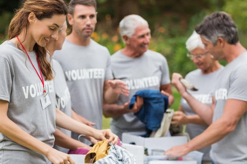 Grupo com seis voluntários usando camisetas cinzas iguais separa roupas em caixas.