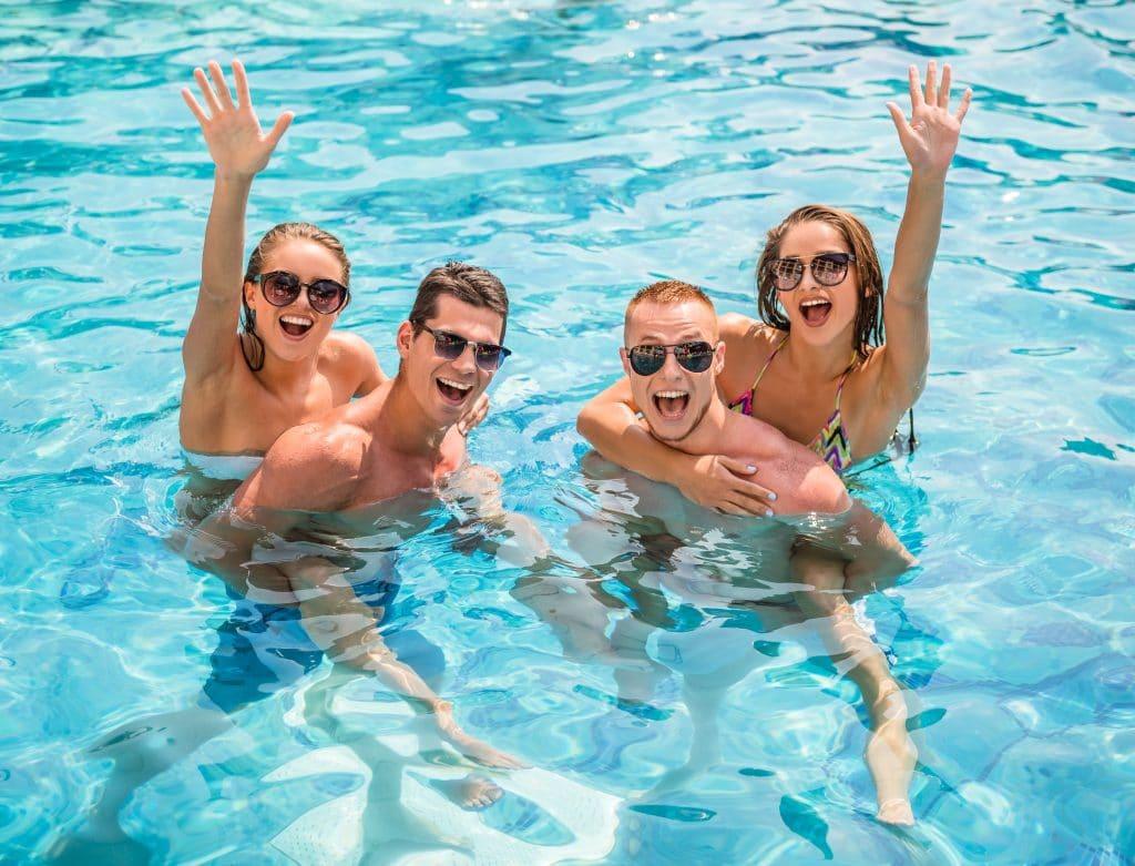 Piscina com 02 casais de homem e mulher. Todos estão dentro da piscina azul, vestindo roupas de banho e óculos de sol. As mulheres estão nas costas dos homens e acenando para a foto.