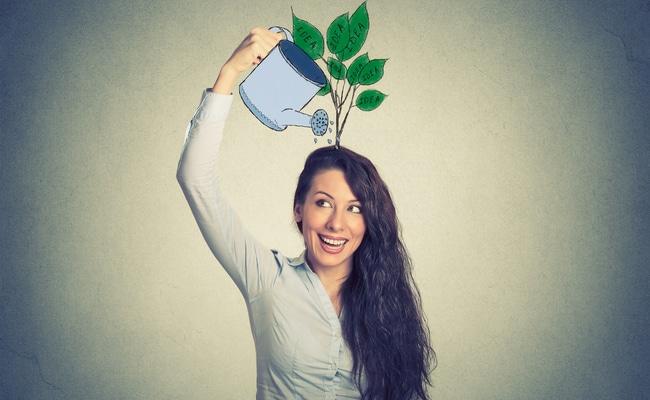 Mulher com a mão direita esticada para cima, e em sua mão foi desenhado um regador. Em sua cabeça foi desenhado um ramo com folhas. O regador está regando a planta.