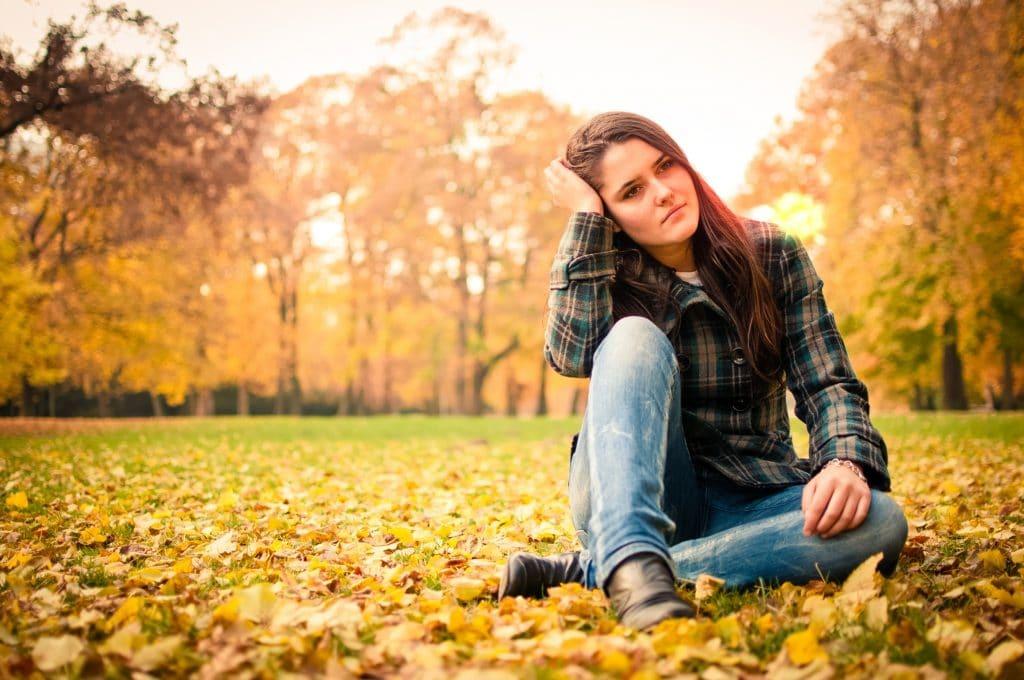 Mulher em estado depressivo. Ela está em um campo sentada sobre folhas caídas no chão. Ela usa calça jeans e camisa xadrez.