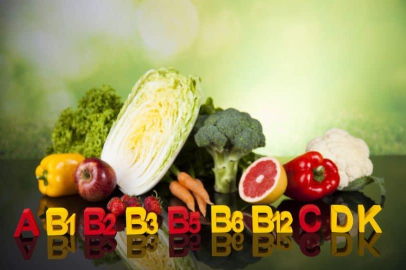 Alguns vegetais e frutas, com vitaminas escritas em fileira na frente deles. As vitaminas são: A, B1, B2, B3, B5, B6, B12, C, D e K.