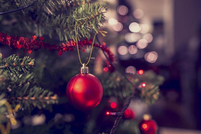 Árvore de Natal decorada com fitas, luzes e enfeites. A foto está bem perto focando em uma bolinha vermelha.