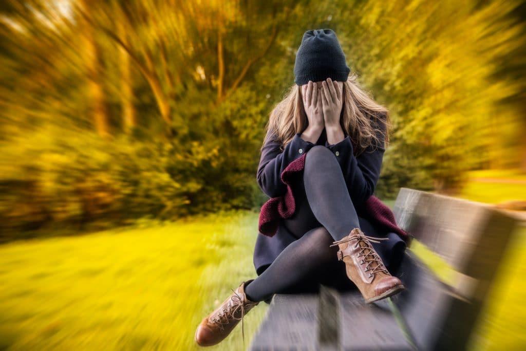 Imagem de uma mulher triste e com as duas mãos sobre o rosto. Ela está sentada em um banco no campo. Está frio. Ela usa roupas de inverno e uma touca de lã preta.