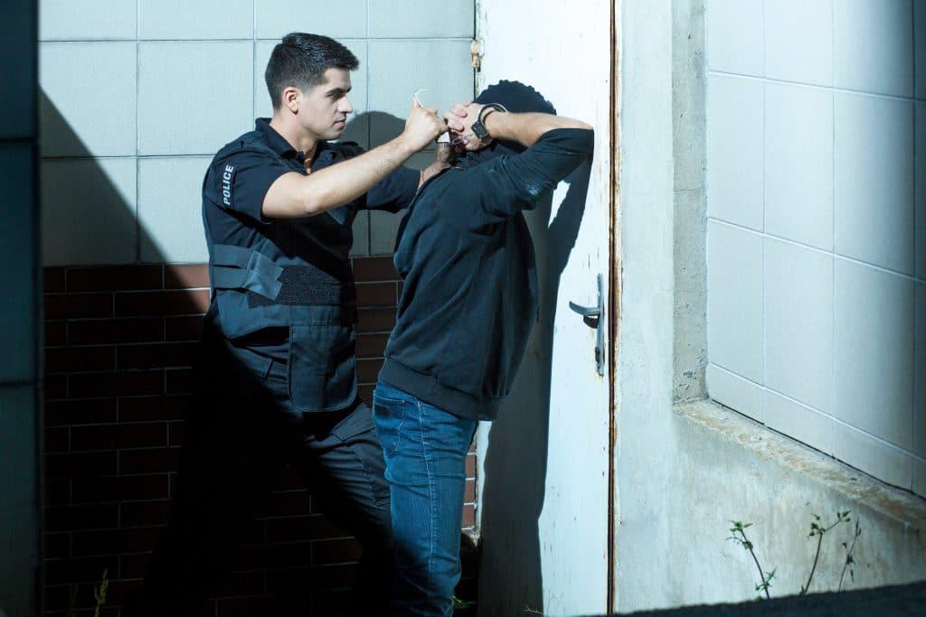 O policial muito corajoso em seu trabalho fazendo abordagem em um homem. O policial enquadrou o homem encostando-o em uma porta e procurou algemá-lo.