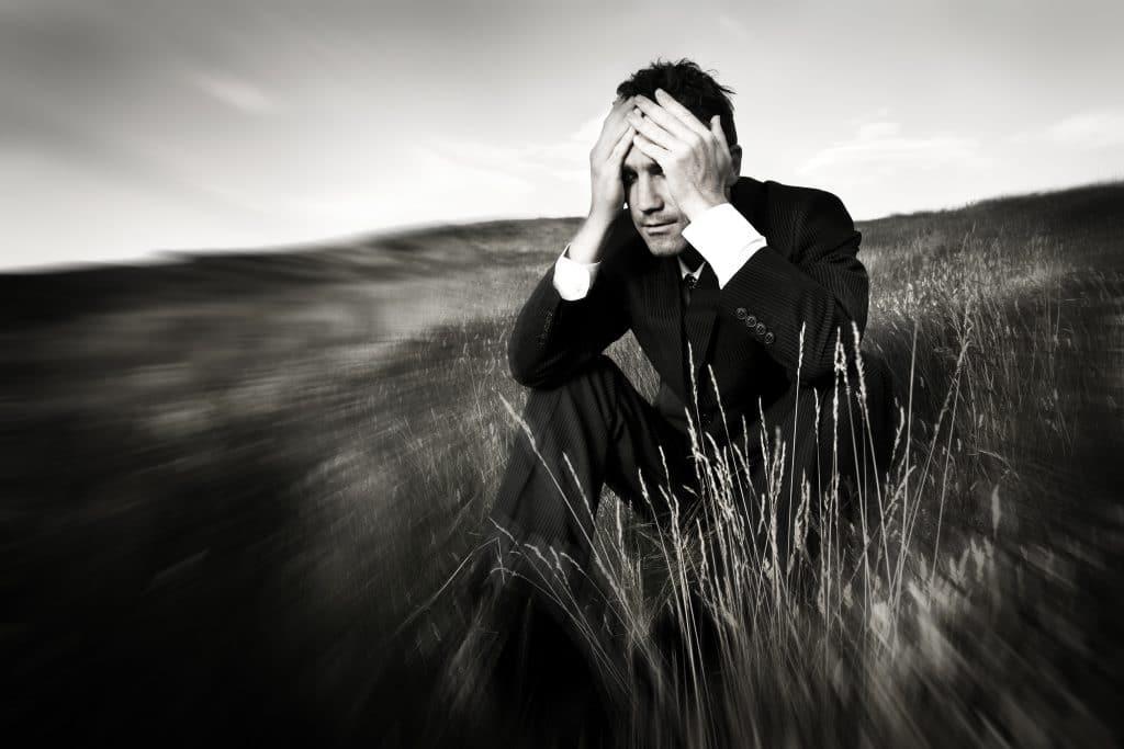Campo aberto com muito gramado e um homem sentado. Ele veste um terno preto e uma camisa branca. Parece estar ansioso. Suas mãos estão sobre a sua cabeça.