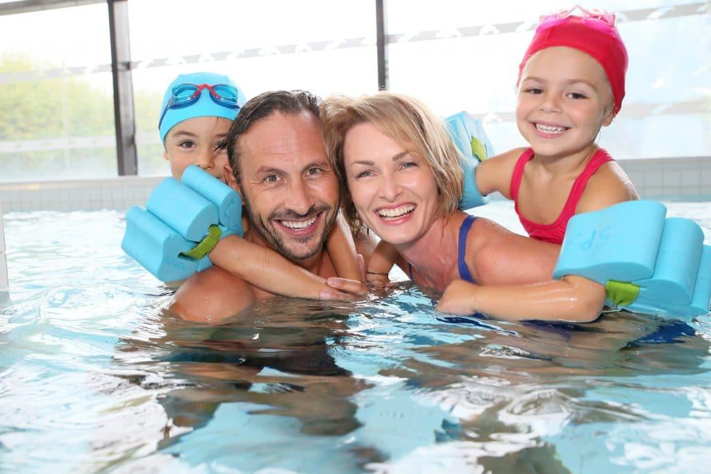 Família composta por um casal de homem e mulher e suas duas filhas pequenas. Eles estao odentro da piscina. As meninas estão usando boias nos braços e toucas nas cores azul claro e laranja.