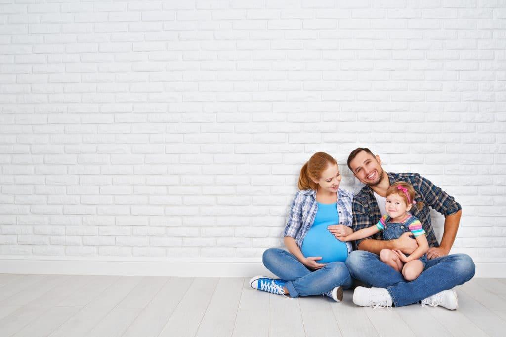 Família reunida sentada no chão. É um casal de homem e mulher e uma criança. A mulher está grávida. Na foto ela segura a sua barriga e a filha menor está sentada no colo do pai.
