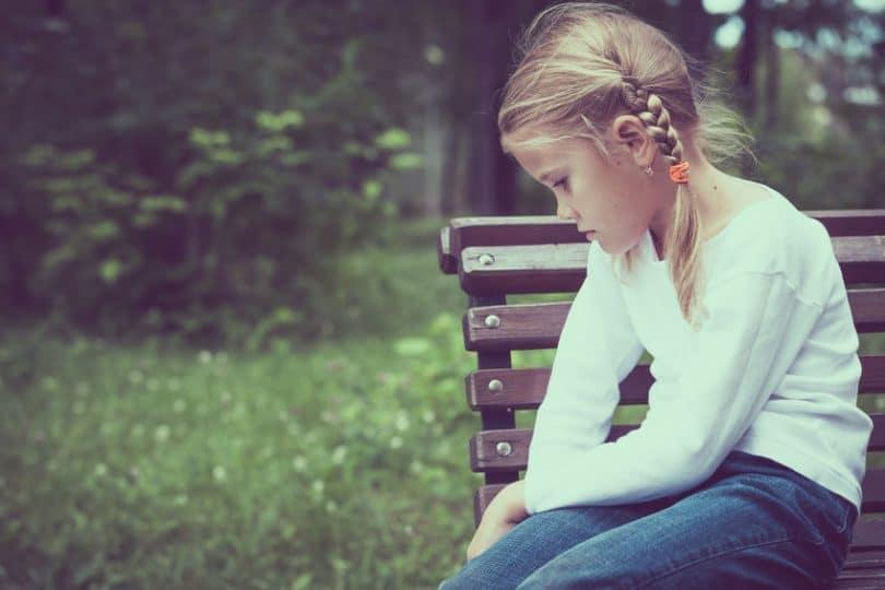 Menina triste sentada em banco de parque, olhando para baixo.