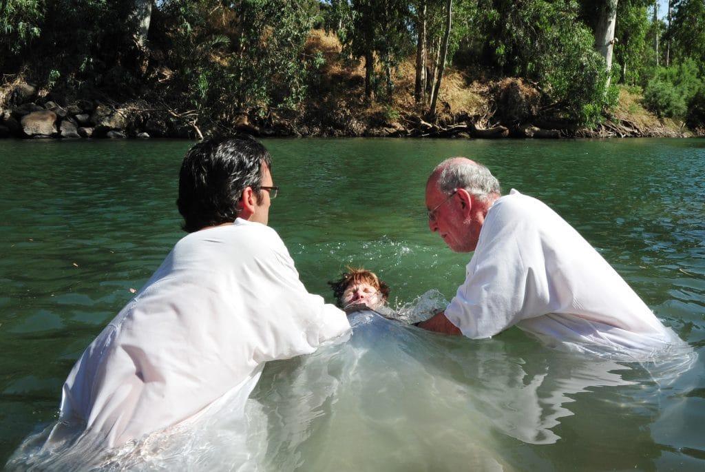 Dois homens com vestes branca reallizando o batismo de uma criança dentro de um rio cercado de uma mata verde.