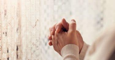 Mãos femininas entrelaçadas em frente a uma cortina branca de renda. Ela aparenta estar rezando.