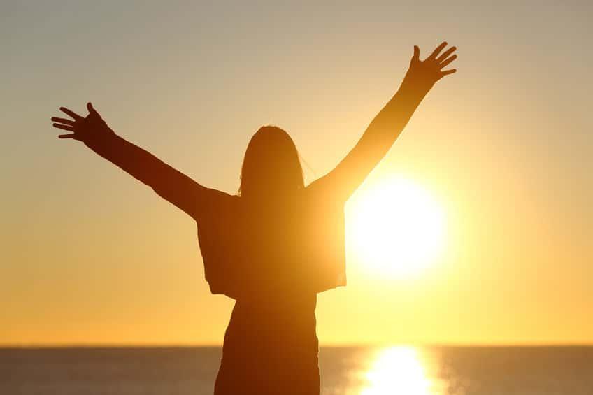 Mulher de frente para o Sol.