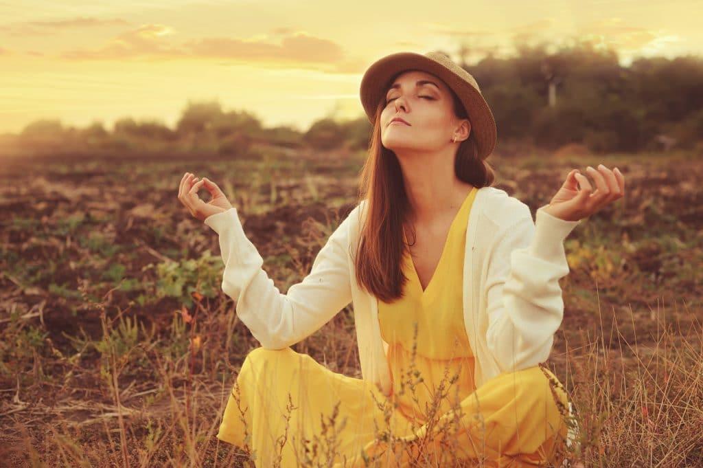 Mulher em posição de meditação. Ela está em um lindo campo cerrado. Ela veste um vestido amarelo, casaco de linha branco e um chapéu de palha.