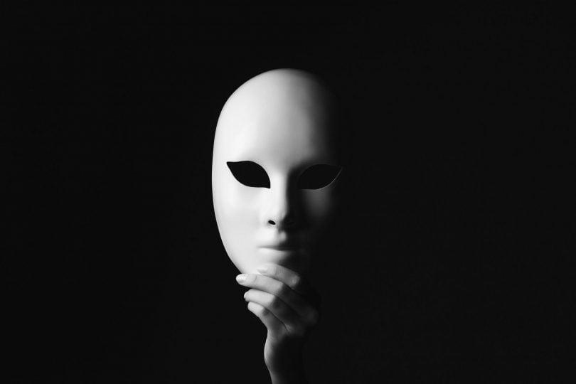 Mão segurando uma máscara plástica no lugar em que estaria seu rosto, escondendo-o.