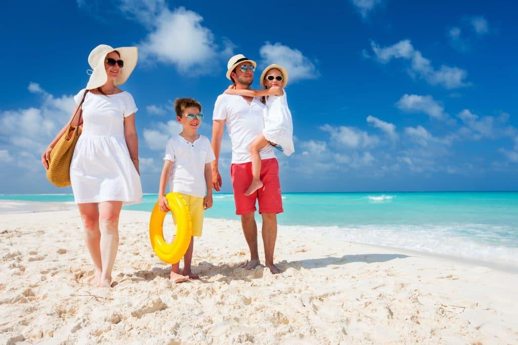 Casal de homem e mulher passeando na areia da praia. Eles estão com seus dois filhos: um menino e uma menina. Tanto a mãe quanto a filha vestem um vestido branco e um chapéu de palha. O pai e o filho vestem camiseta branca e bermudas nas cores laranja e amarela. O menino carrega uma boia amarela em uma das mãos e a menina está no colo do pai.