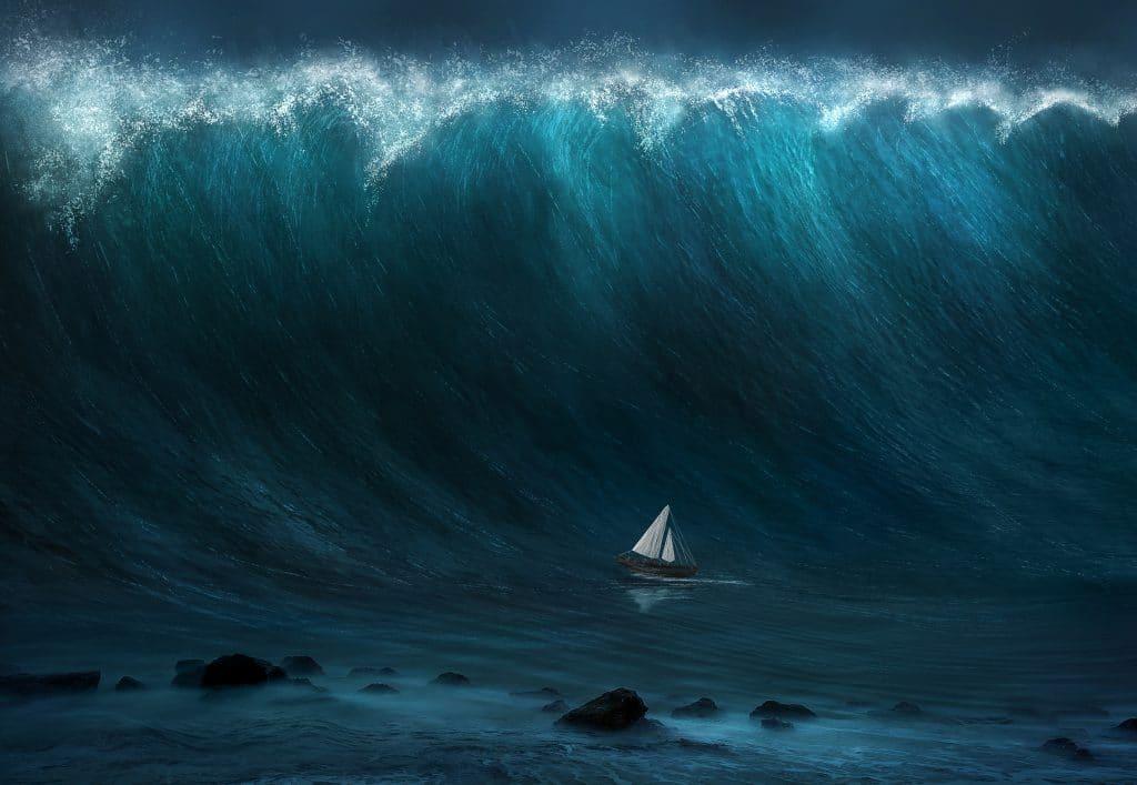 Onda gigante se formando e bem abaixo dela um barquinho de vela branca.