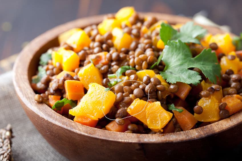 Salada de lentilha com legumes em uma tigela de madeira.