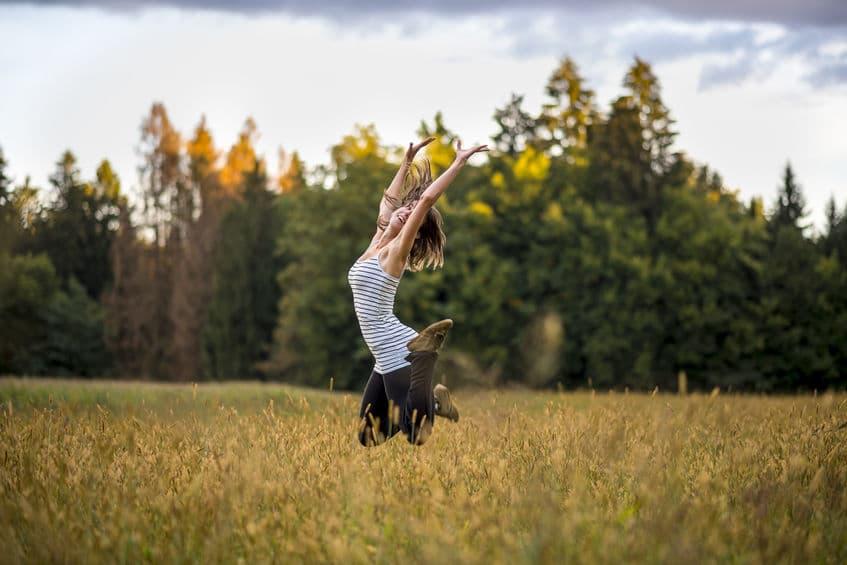 Moça pulando em campina, com os braços para cima. Suas pernas estão flexionadas para trás enquanto ela está no ar.