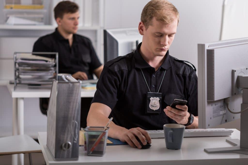 Dois homems policiais brancos trabalhando no escritório da corporação da polícia. Ambos estão sentados em frente aos computadores. Um deles está fazendo uma ligação ao telefone celular.