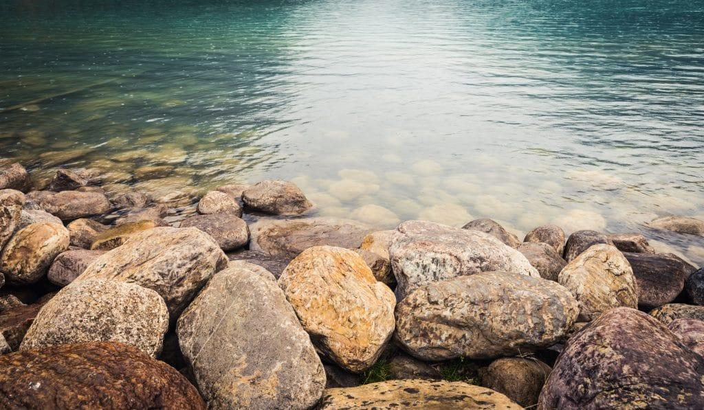 Lago com uma água bem límpida. Várias pedras compõem o visual do lago e da água.