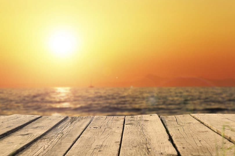 Imagem do mar com um sol forte e laranja no horizonte.