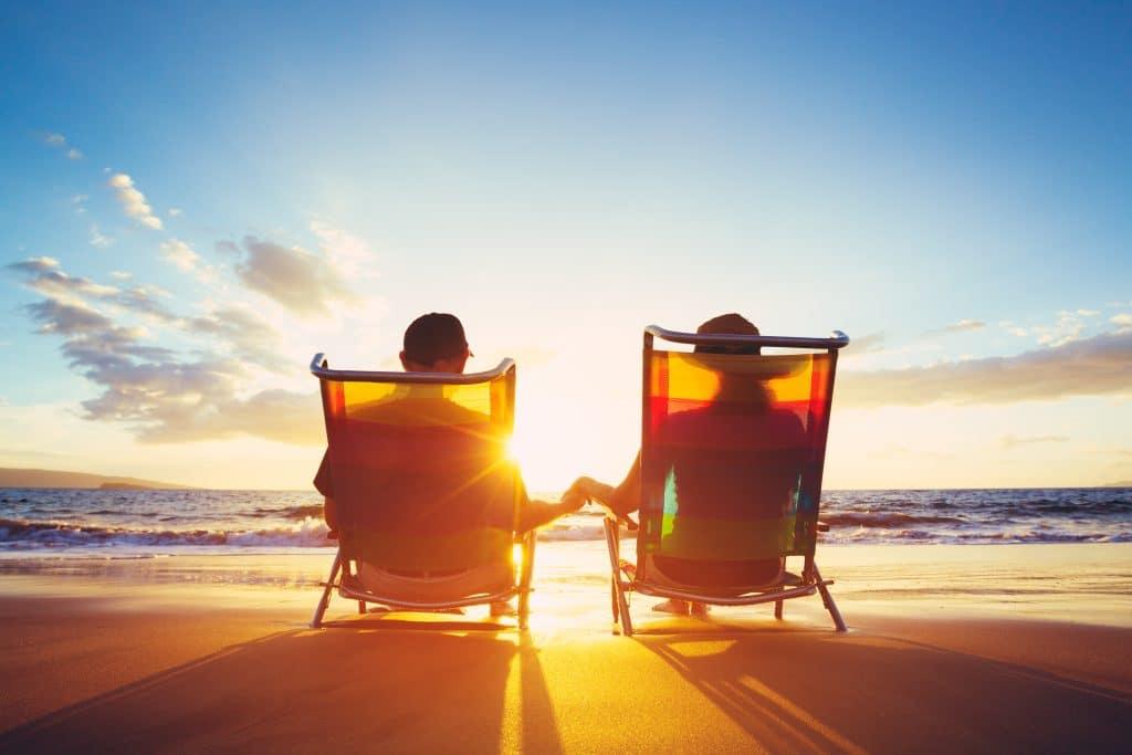 Casal sentado em uma cadeira de praia olhando para o mar. Eles estão apreciando o por do sol.