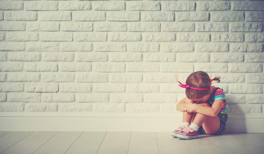 Criança menina, sentada no chão. Ela está chorando. Ao fundo uma parede de tijolinho branca.