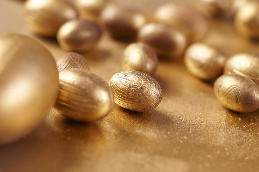 Vários ovos de páscoa de chocolate na cor dourada. Todos estão dispostos sobre uma mesa também dourada.