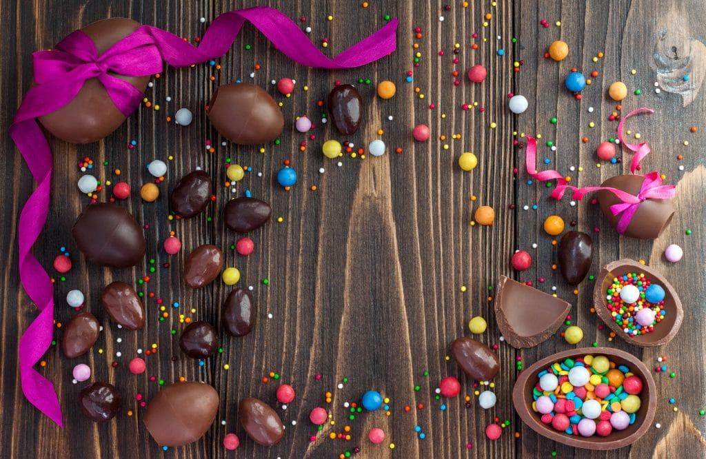 Muitos ovos de páscoa de chocolate. Alguns estão inteiros e outros cortados ao meio e recheados com muito confete colorido e bombons. Ao fundo temos um ovo de páscoa grande embrulhado com um laço de fita na cor roxa.