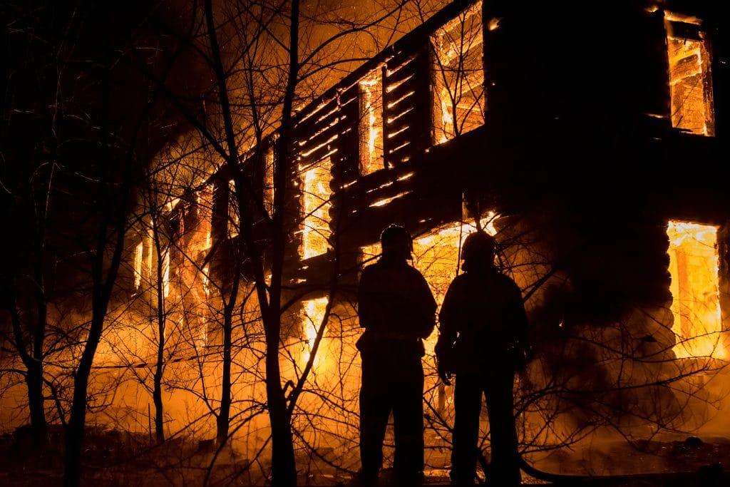 Casa sendo totalmente consumida pelo fogo e dois homens observando a tragédia sem poder fazer algo.