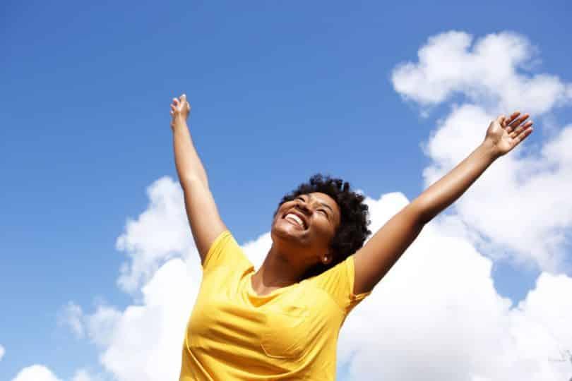 Mulher em pé sorrindo com braços para cima e céu azul com nuvens ao fundo
