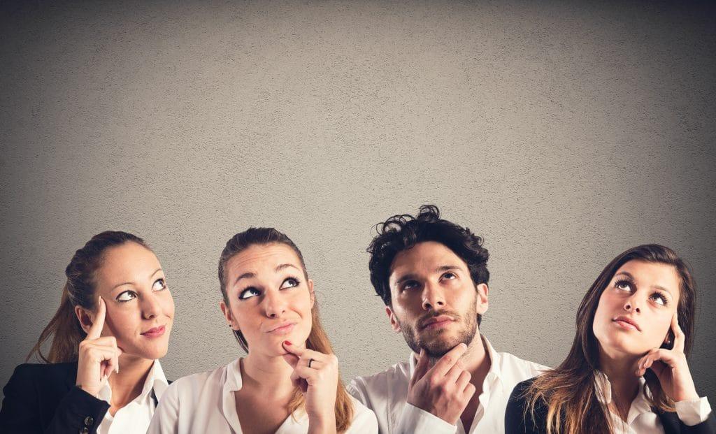 Três mulheres e um homem. Todos eles estão com uma expressão pensativa. Duas mulheres estão com uma das mãos segurando o rosto e o homem e a outra mulher com uma das mãos segurando o queixo.