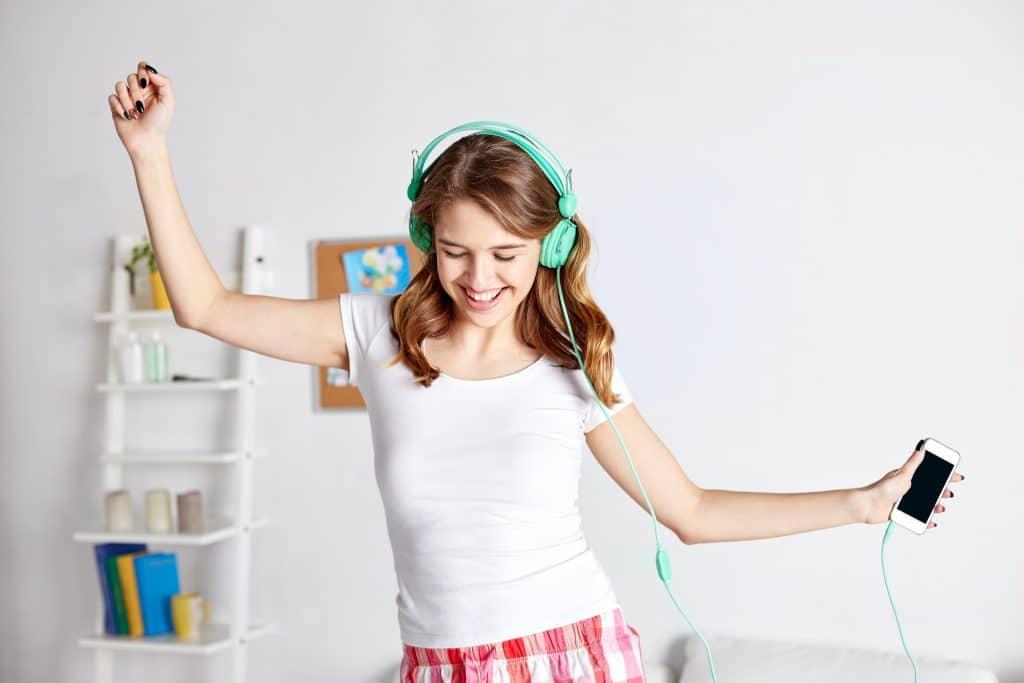 Mulher jovem e feliz. Ela está dançando ouvindo a sua música favorita no seu celular com o seu fone de ouvido azul. Ela veste uma camiseta branca e um shorts xadrez as cores vermelho e branco.