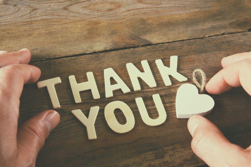Palavra Thank You escrita em branco em uma base de madeira. A palavra foi formada pelas mãos de um homem que está finalizando com um coração decorativo pequeno feito em madeira e pintado na cor branco.