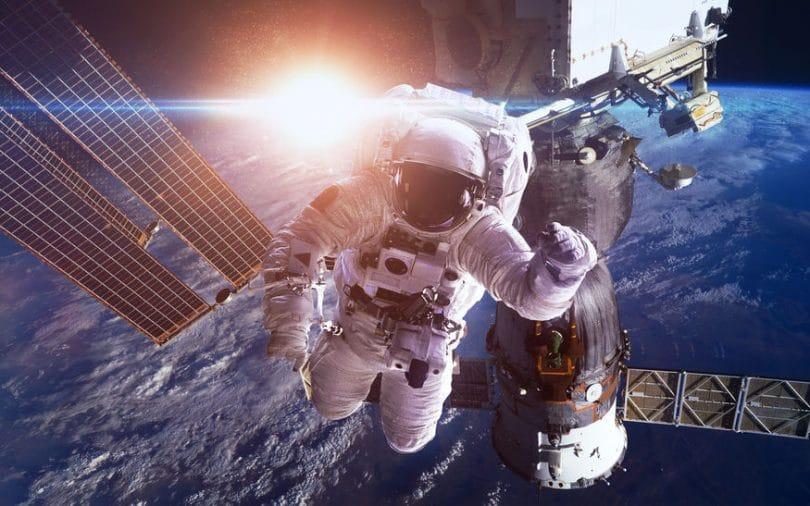 Imagem manipulada de astronauta no espaço, entre um satélite e a Estação Espacial Internacional. Ao fundo, é possível ver o planeta Terra bem perto, e atrás dele, o sol brilhando.