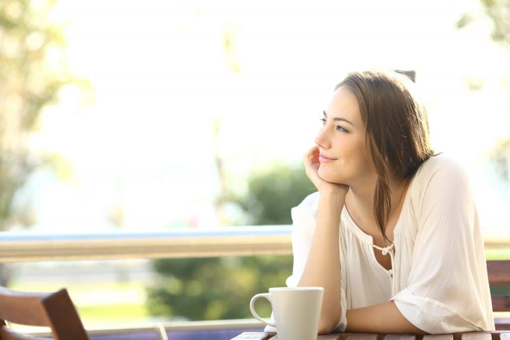 Mulher sorrindo e feliz. Ela está pensativa e olhando para o lado. Está sentada e sobre a mesa uma xícara branca com um saboroso café.