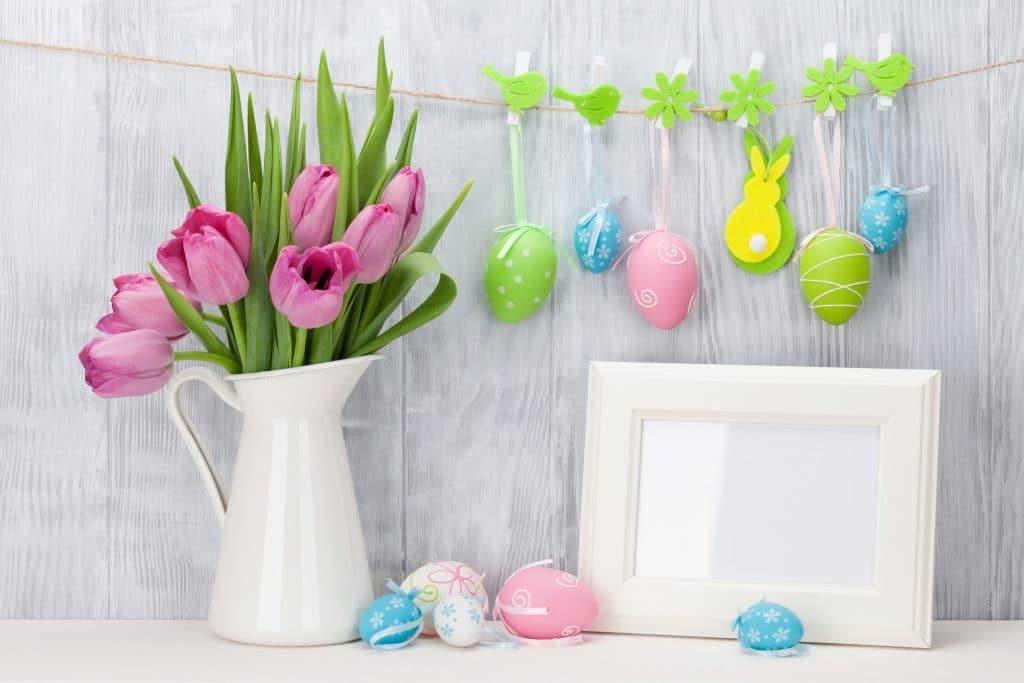 Vaso de porcelana branco com tulipas rosas. Ao lado alguns ovos de páscoas feitos de pano e um porta retrato branco. Ao fundo um varão feito de barbante e neles estão pendurados alguns ovos de páscoa feitos de feltro. São alegres e coloridos.