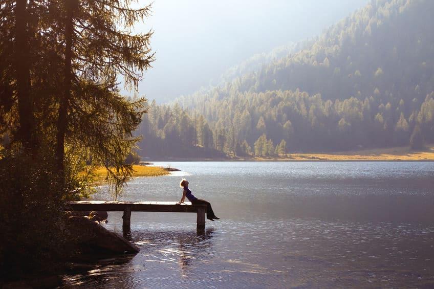 Mulher sentada em ponta de pier, se apoiando nos braços que estão esticados para trás. O pier está em um lago, e ao fundo é possível ver montanhas.