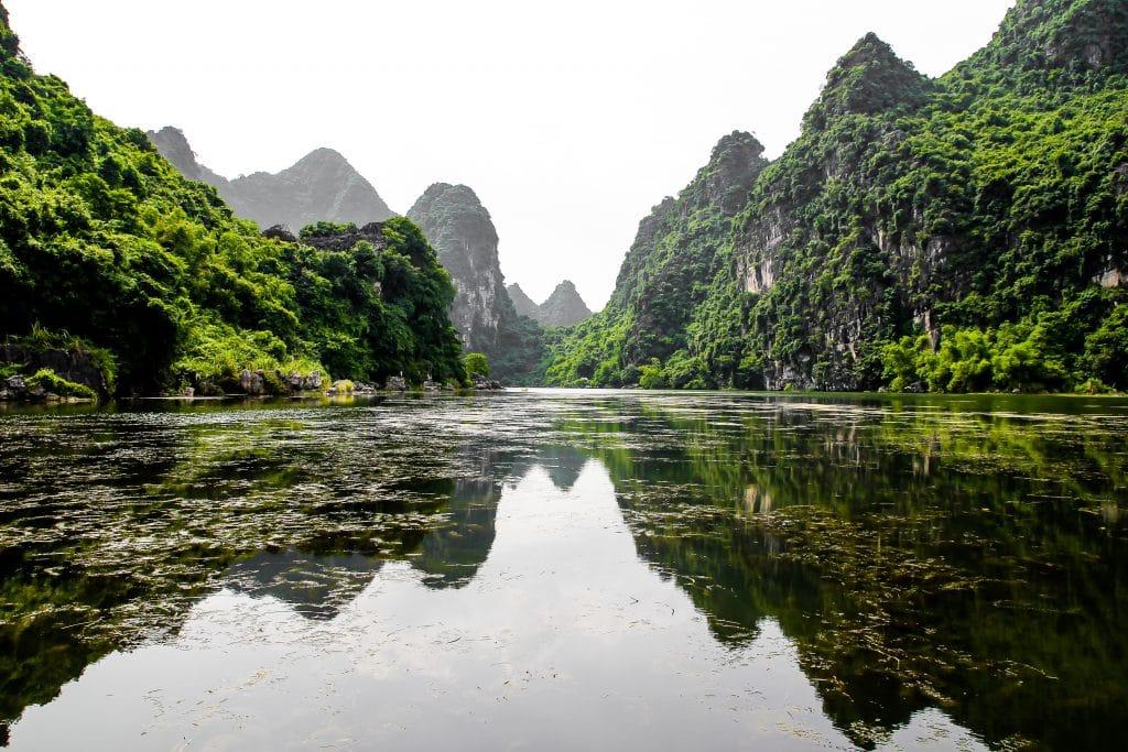 Lago bem grande com uma água límpida. Em volta do lago várias montanhas rochadas e verdes.