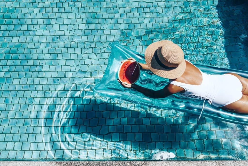 Mulher vestindo um maio branco e um chapeu de palha. Ela está deitada de bruço sobre uma boia plástica na cor azul sobre uma piscina bem limpa. Ela está saboreando um pedaço de melancia.