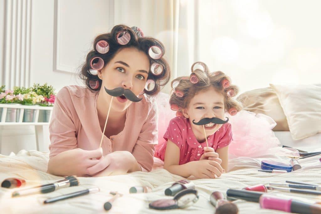 Mãe e filha deitadas sobre a cama. Elas estão usando bobs nos cabelos e segurando uma máscara de bigode. A cama está repleta de itens de maquiagem. É uma imagem alegre e descontraída onde ambas celebram o dia das mães.