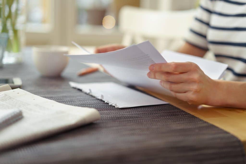 Mulher vestindo uma camiseta branca com listras preta. Ela está sentada próxima a uma mesa e lendo uma mensagem espírita.