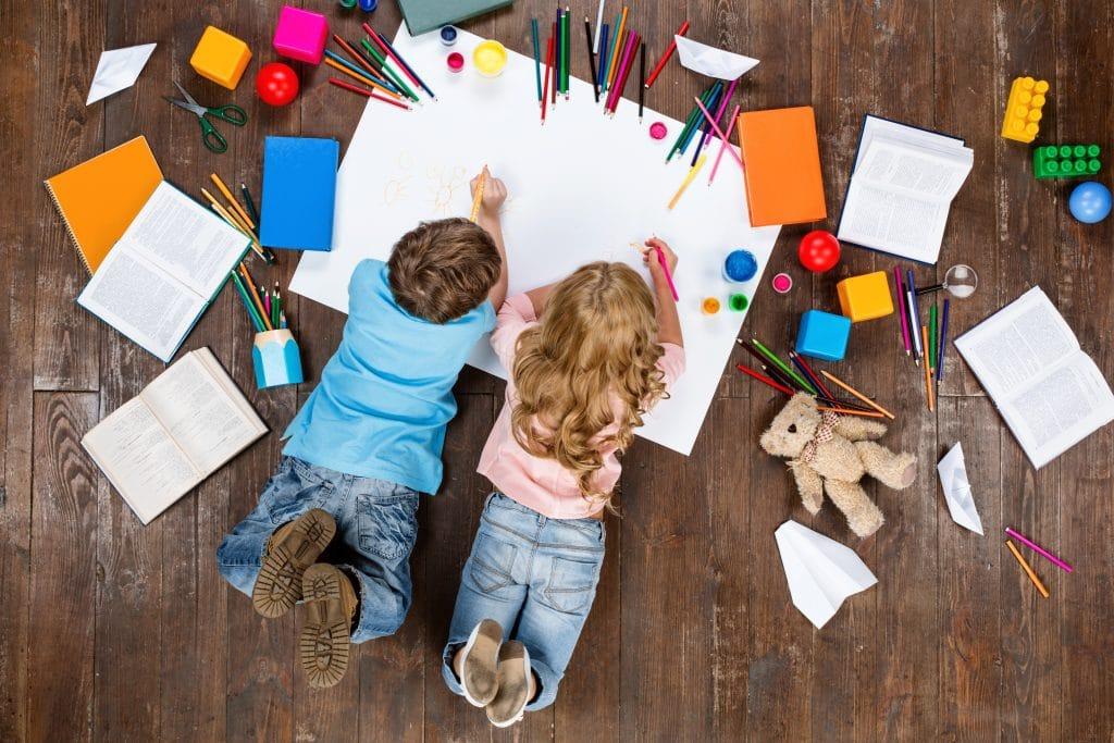 Duas crianças (um menino e um menina) deitadas de bruços sobre uma cartolina branca. Ela estão desenhando e pintando. Em volta vários livros, lápis coloridos e brinquendos espalhados no chão de madeira escuro.