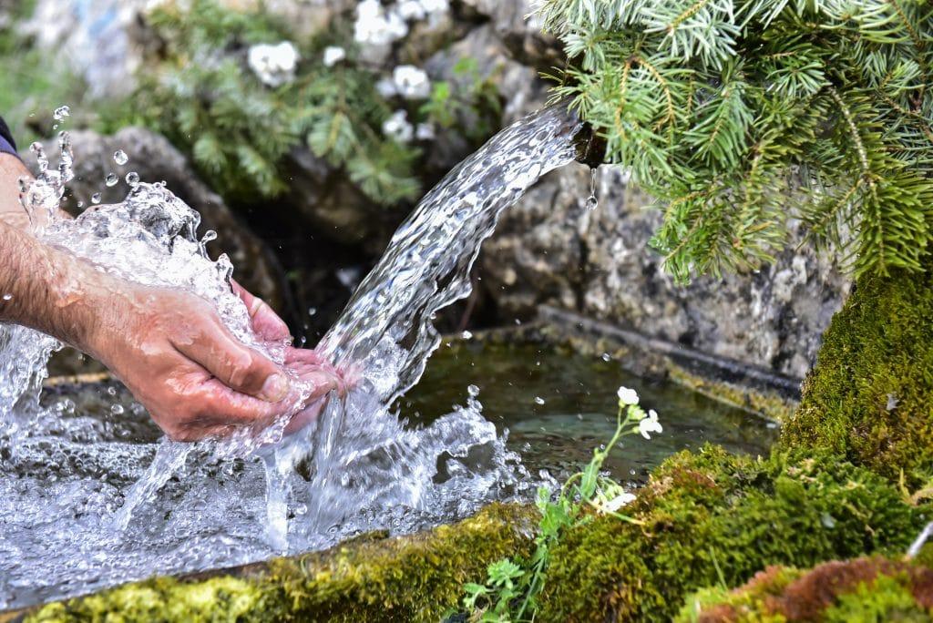 Fonte jorrando uma água bem limpinha. Essa água está sendo desaguada no rio. Mãos masculinas estão tocando a água que sai da fonte. A fonte está rodeada de verde.
